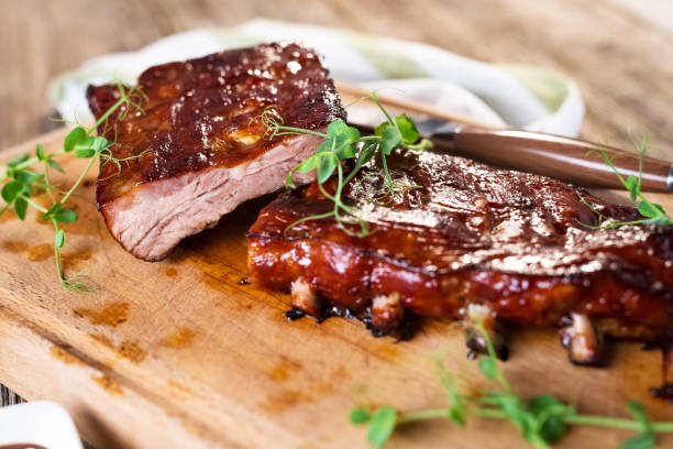 smoked barbecue pork spare ribs - ribs stock photos and pictures