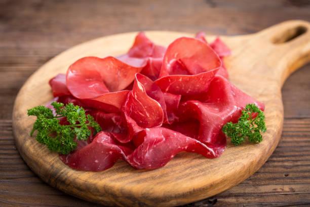smoked beef prosciutto, sliced bresaola on a wooden board - bresaola foto e immagini stock