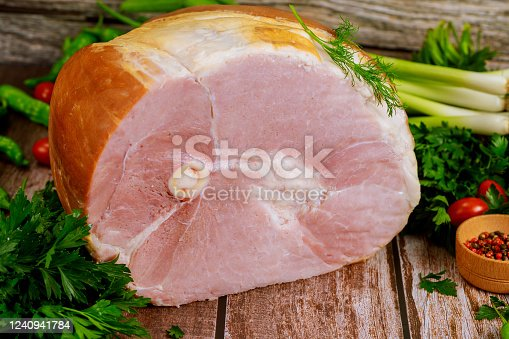Smoked bone in ham with vegetables and spice on wooden Christmas table. Close up.