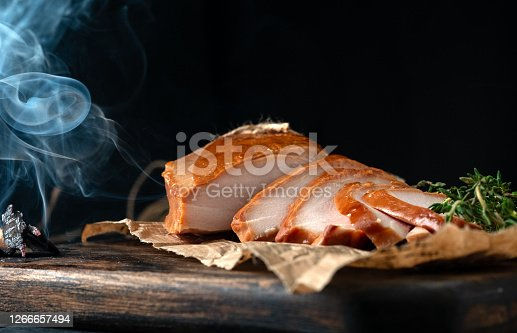 Smoked breast chicken fillet whole and sliced on wooden board. Rustic natural food