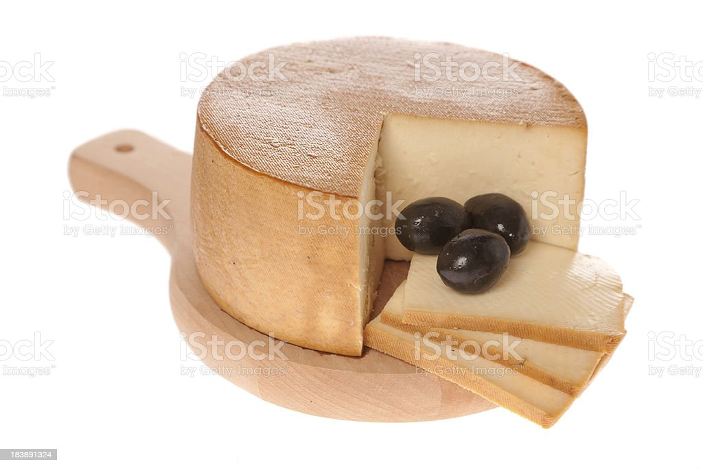 Smoked cheese on cutting board with black olives isolated royalty-free stock photo