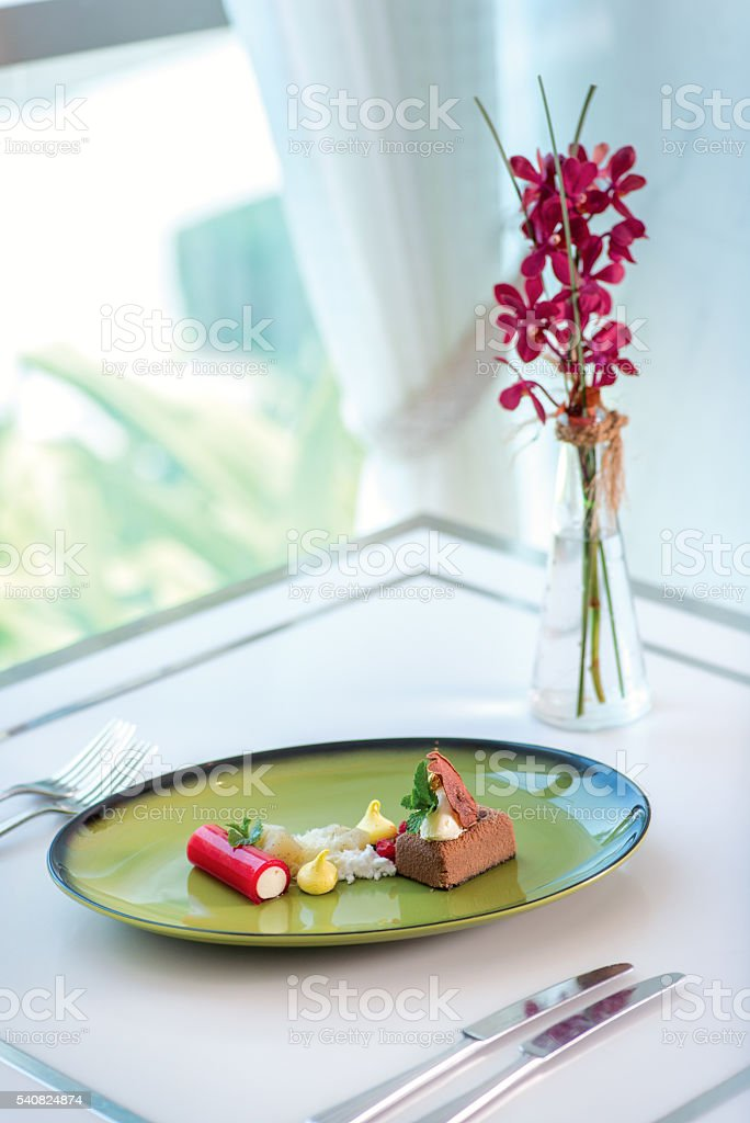 Smoked chocolate mousse, poached pear, chantily-raspberry log. D stock photo