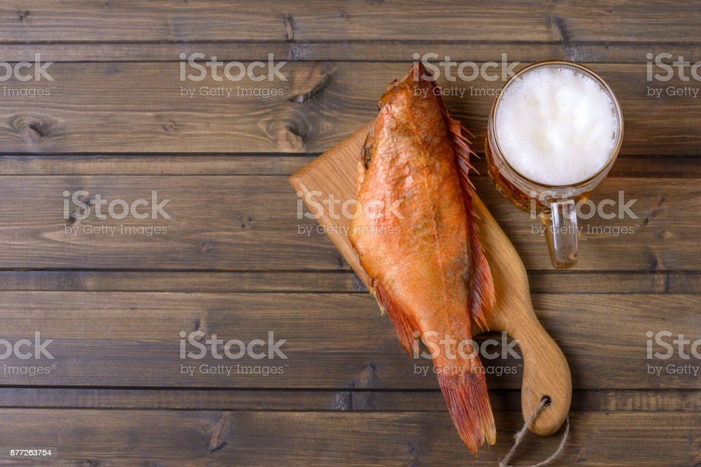 Smoked fish and fresh beer on wooden table stock photo