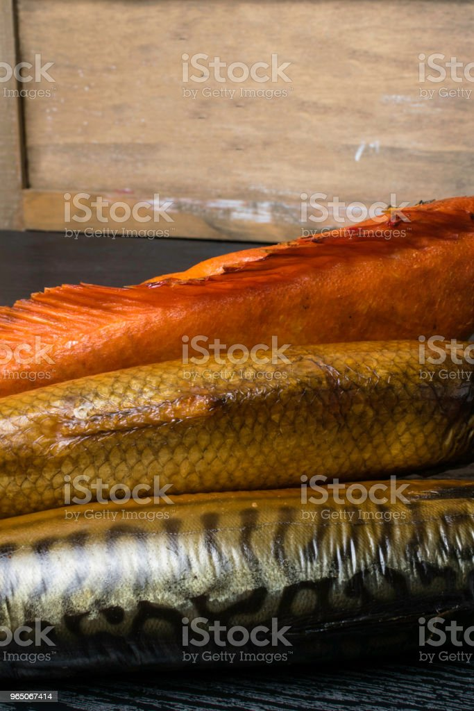 Smoked fish, mackerel, sig and perch on the black wooden table in market zbiór zdjęć royalty-free