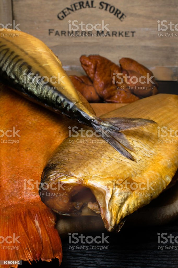 Smoked fish, mackerel, sig, perch and cod roe on the black wooden table royalty-free stock photo
