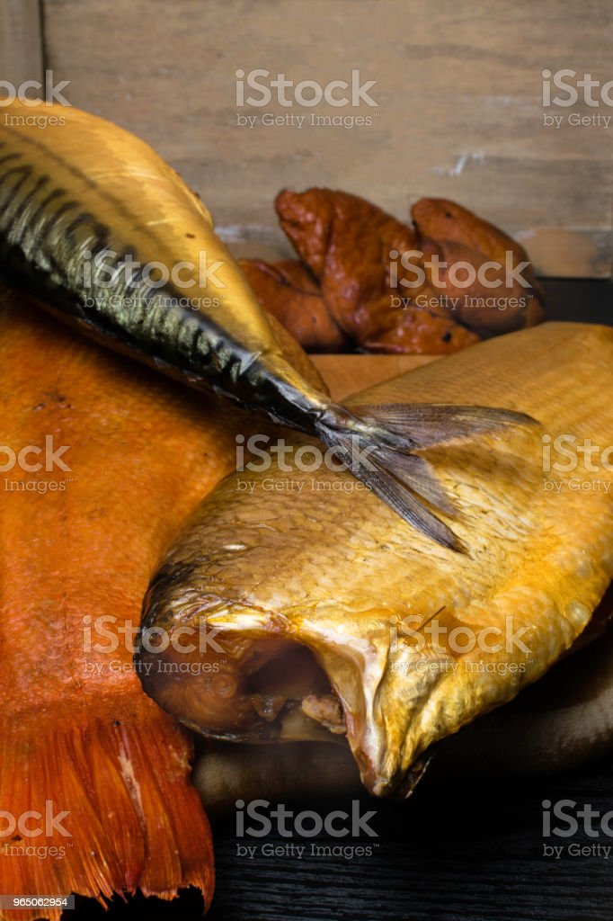 Smoked fish, mackerel, sig, perch and cod roe on the black wooden table. Omega 3 source. Polyunsaturated fats royalty-free stock photo