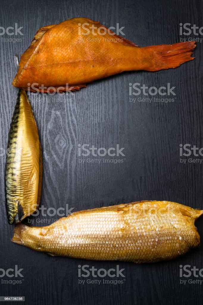 Smoked fish on the wooden table. royalty-free stock photo