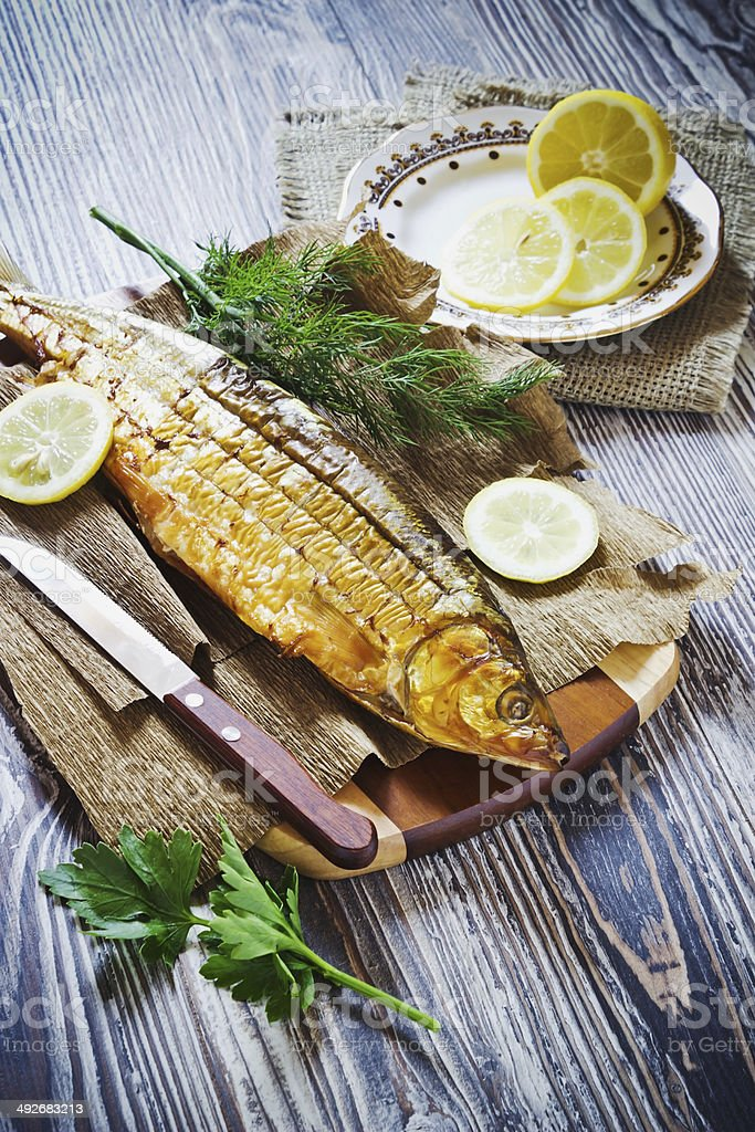 smoked fish with lemon, dill and parsley stock photo