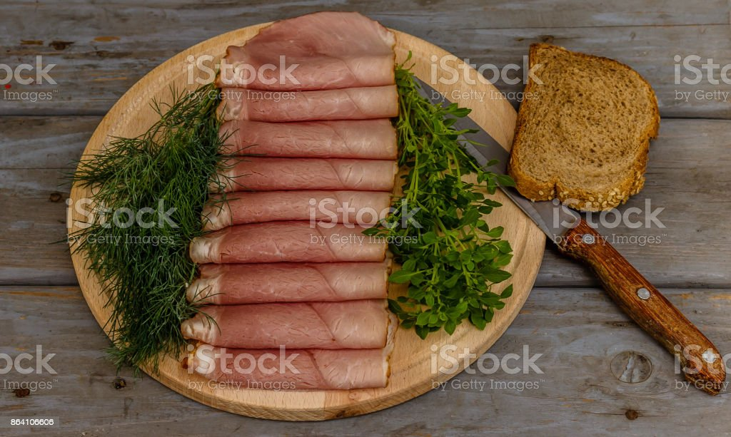 Smoked ham, basil, dill, bread, and knife on a wooden plate on wooden background royalty-free stock photo