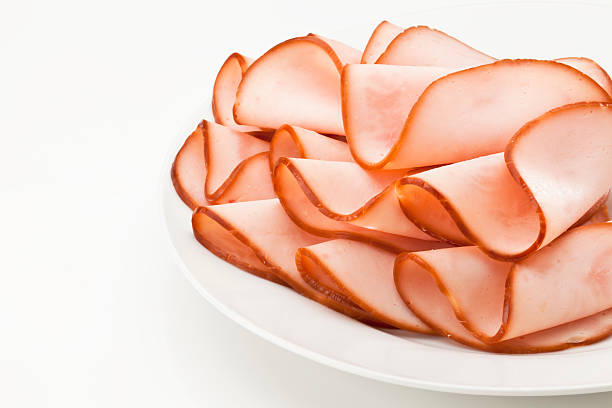 smoked ham slices on a plate - delis stock photos and pictures