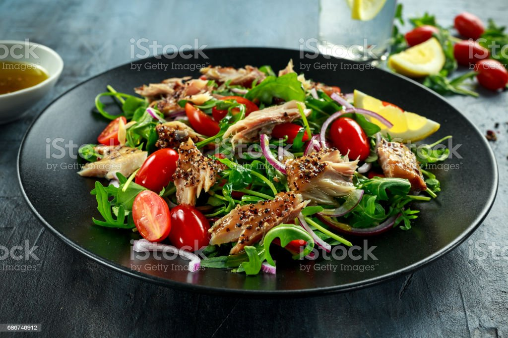 Smoked Mackerel Salad with tomato, chopped red onion, Ruccola on black plate. stock photo