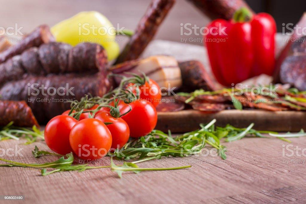 Smoked meat and cherry tomato stock photo