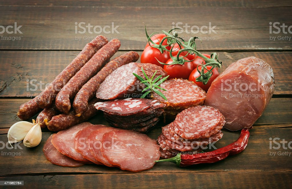 Smoked meats with rosemary and tomatoes stock photo