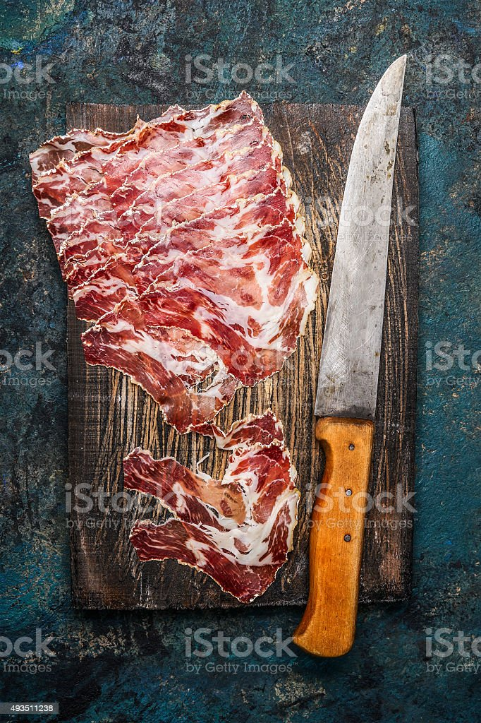 Smoked pork meat from coppa with kitchen knife stock photo
