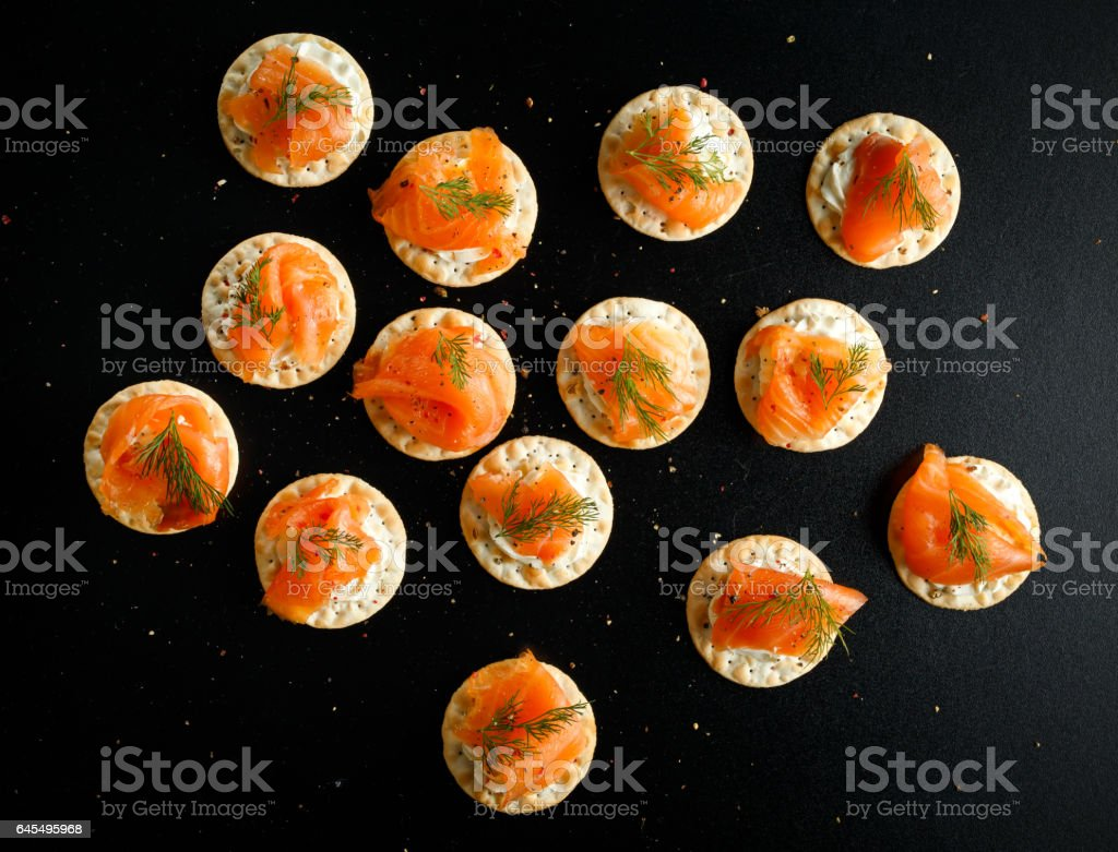 Smoked Salmon and soft chees canapes appetizers with chives on black table – Foto