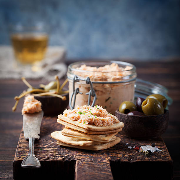 Smoked salmon and soft cheese spread, mousse Smoked salmon and soft cheese spread, mousse, pate in a jar with crackers, olives and capers on a wooden background tuna seafood stock pictures, royalty-free photos & images