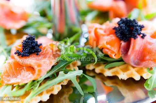 Smoked salmon, caviar, and arugula appetizer on a waffle biscuit.