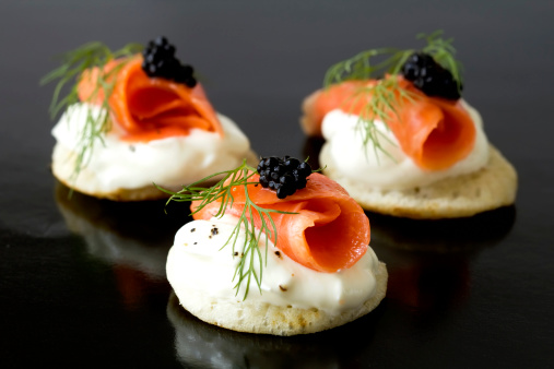 Three smoked salmon blinis with caviar and a sprig of fresh dill.