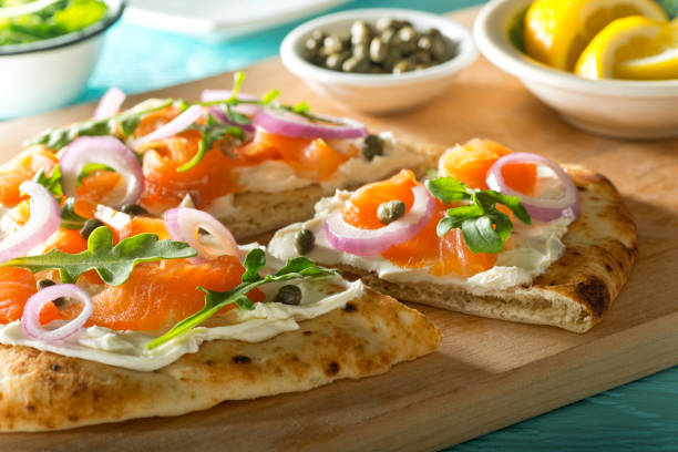 räucherlachs-pizza - fladenbrotpizza stock-fotos und bilder