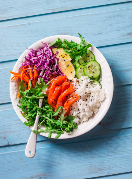 Smoked salmon, rice, vegetables buddha power bowl on blue background, top view. Red cabbage, carrots, arugula, rice, smoked salmon fish bow stock photo