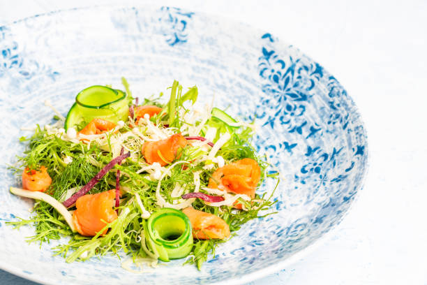 Smoked salmon salad with Arugula, apple, enoki mushrooms, zucchini and beetroot on a white and blue plate over a blue background. stock photo