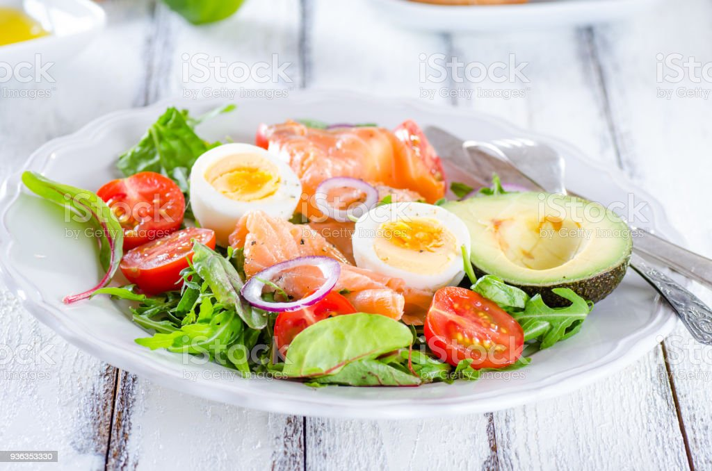 Smoked salmon salad with greens, tomatoes, eggs and avocado stock photo