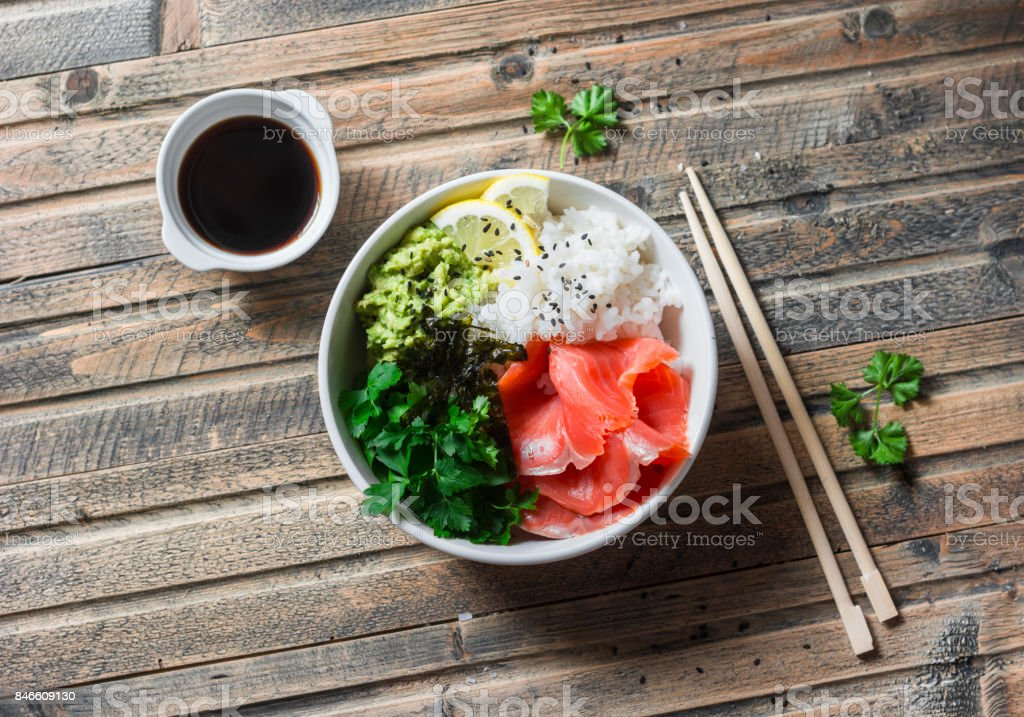 Smoked salmon sushi bowl on wooden background, top view. Rice, avocado puree, salmon - healthy food concept stock photo
