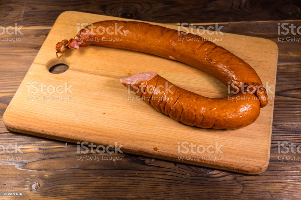 Smoked sausage on cutting board on wooden table stock photo