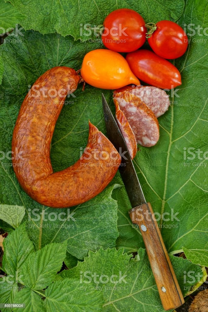 Smoked sausage with a knife and fresh vegetables on a green leaf stock photo