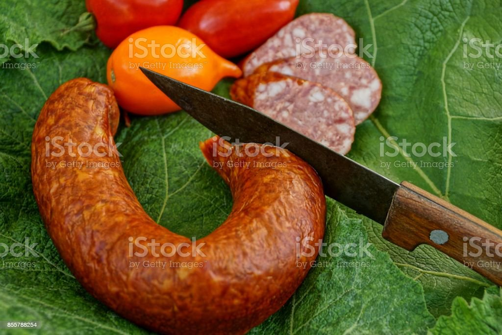 Smoked sausage with a knife and ripe tomatoes on a green leaf stock photo