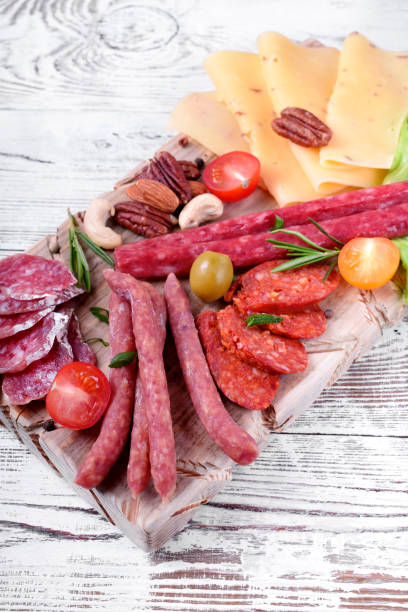 surtido de salchichas ahumadas, queso, nueces, tomates cherry, verduras enescabezadas y aceitunas en la mesa de madera blanca - fuet sausages fotografías e imágenes de stock