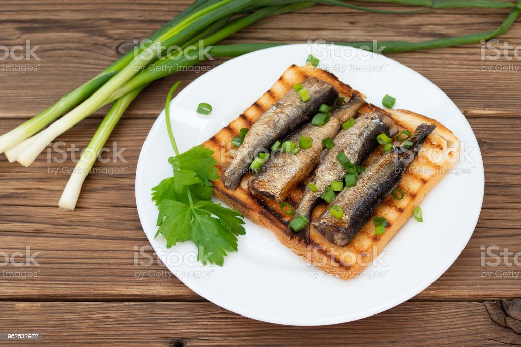 Smoked sprats on toast with parsley and leek on wooden background. - Royalty-free Backgrounds Stock Photo