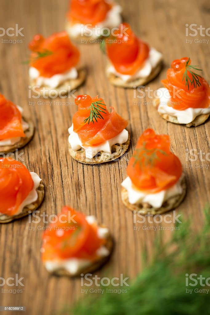 Smoked Trout bite size starters on a wooden table stock photo