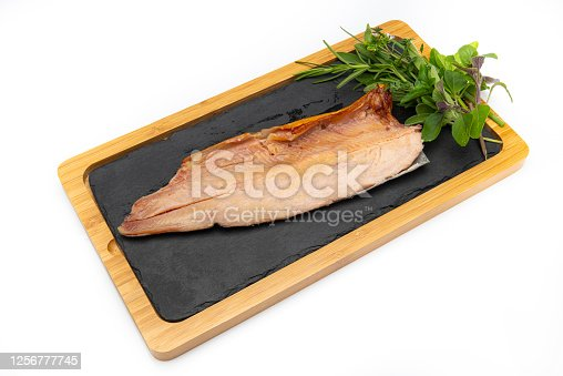 Image of a smoked rainbow trout over a bamboo and black stone tray with rosemary and basil