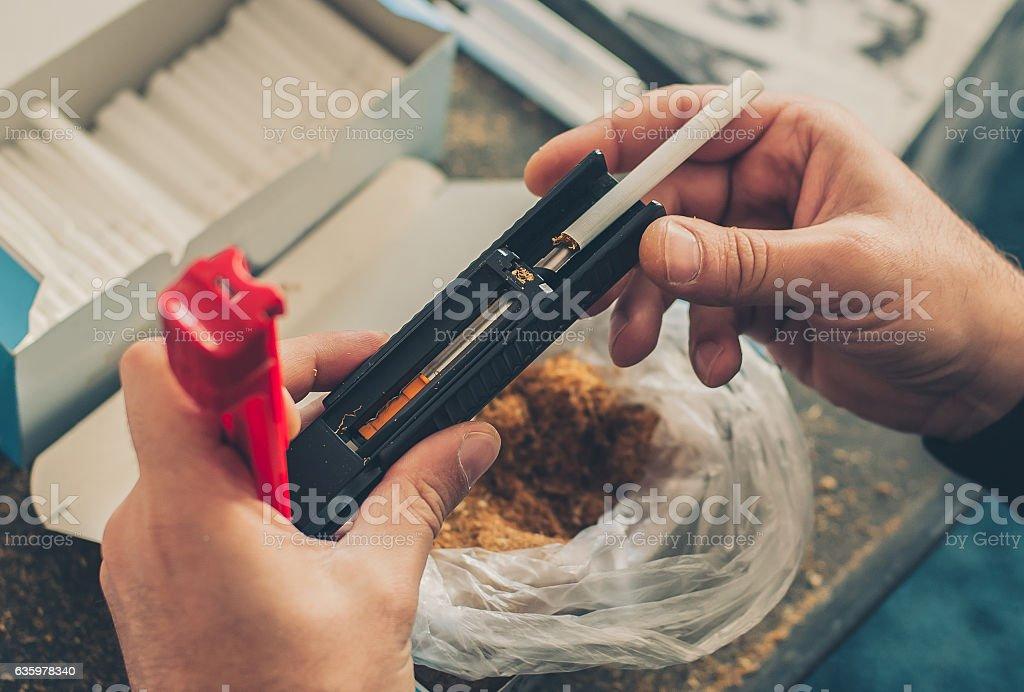 Smoker man roll tobacco cigarettes using rolling machine stock photo