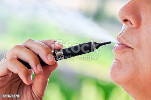 istock Smoker of Electronic Cigarette with steam 482674475