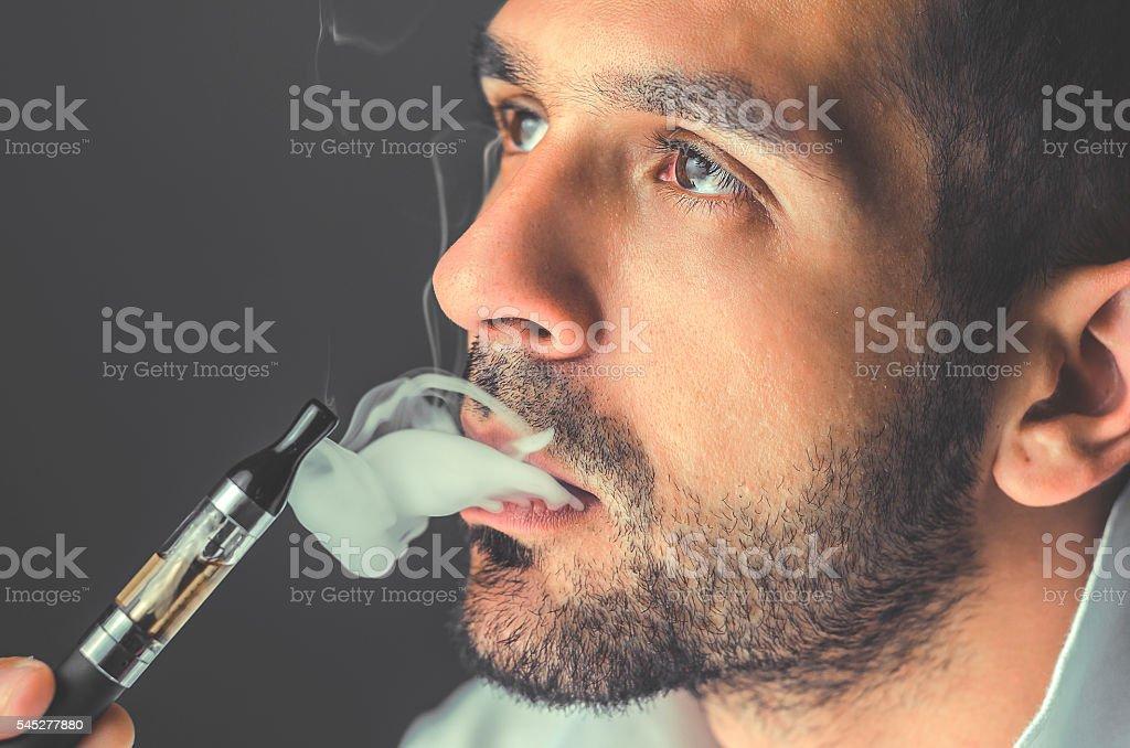 smoker smokes an electronic cigarette - foto de acervo