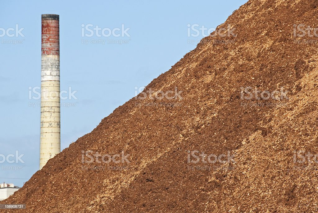 Smokestack at pulp mill and sawdust pile stock photo