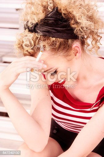 Stunning BLond who has her hair pulled up in tight little curls - smoking a cigarette.  She seems shy as she shields her face from something or someone smiling quietly to herself.  Red and White Stripped Sweater and black high waisted button shorts.