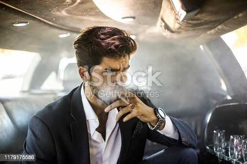 Businessman driving in a limousine. About 30 years old, Caucasian male.