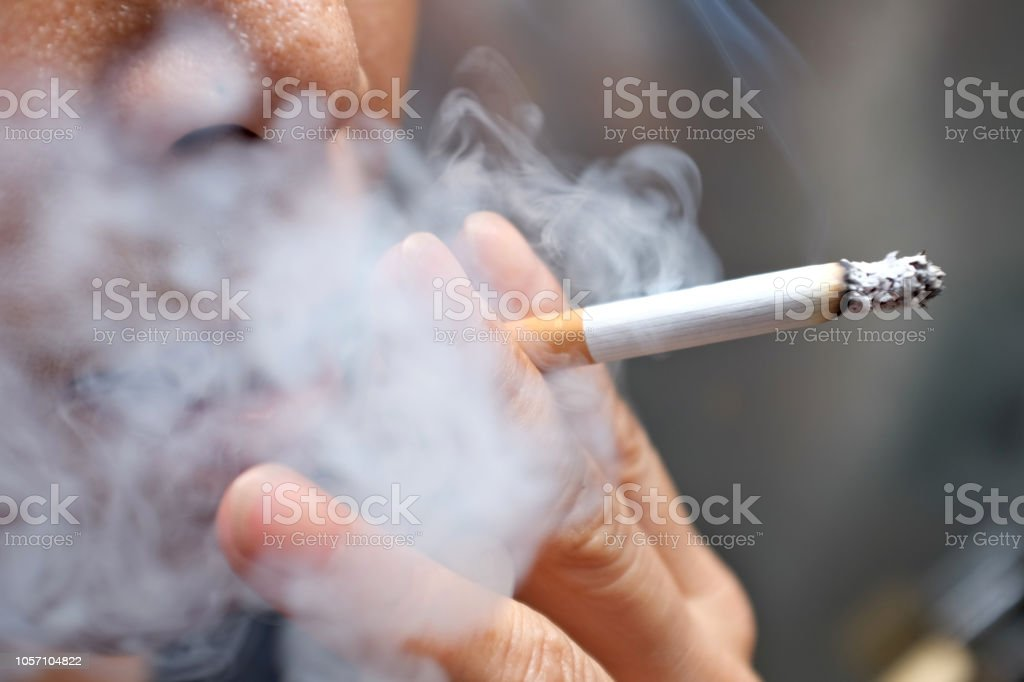 Smoking a cigarette Smoking a cigarette with smoke around and a blurred background Addiction Stock Photo