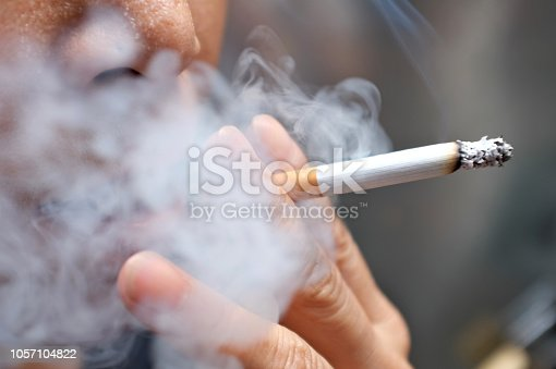 Smoking a cigarette with smoke around and a blurred background