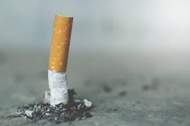 smoking a cigarette. pulverize the floor. - cicca sigaretta foto e immagini stock