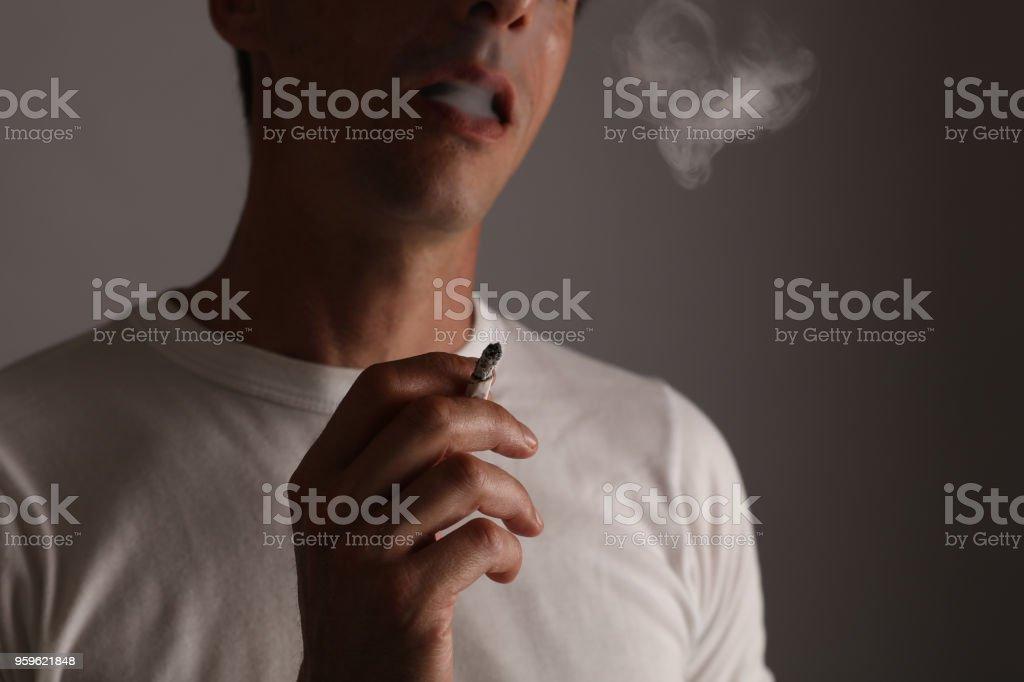 Concepto de la adicción de fumar. Fumar cigarrillo de hombre y hace forma de humo - Foto de stock de Adicción libre de derechos