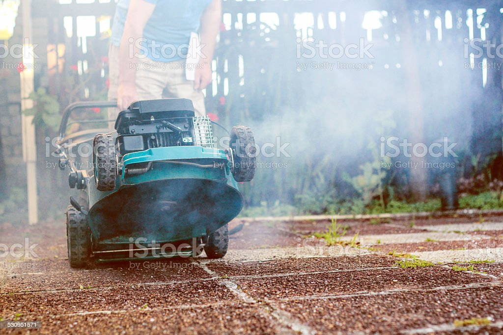 Smoking and crazy broken lawnmower stock photo