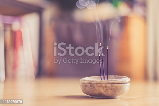 Joss sticks in smoking bowl are smoking and smelling, home, feng shui; Copy space;