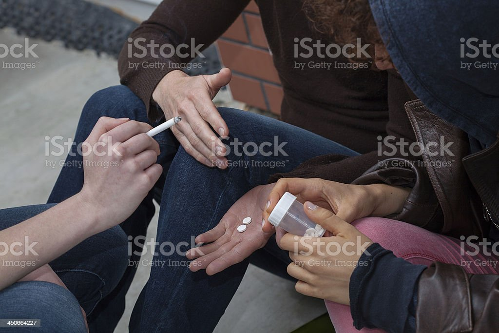Smoking and taking pills stock photo