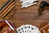 Smoking and tobacco products, cigars, cigarettes and a pipe with tobacco, on top of a wooden background, with playing cards, ashtray and alcoholic drink