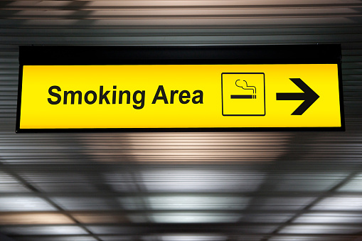 smoking area sign with icon and arrow pointing to smoking area zone hanging from airport ceiling at international terminal. designated smoking areas for separate the smokers from the non-smoking zone