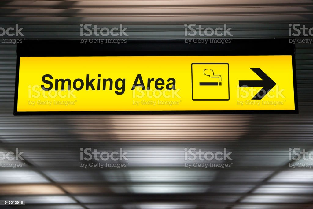 smoking area sign with icon and arrow pointing to smoking area zone hanging from airport ceiling at international terminal. designated smoking areas for separate the smokers from the non-smoking zone stock photo